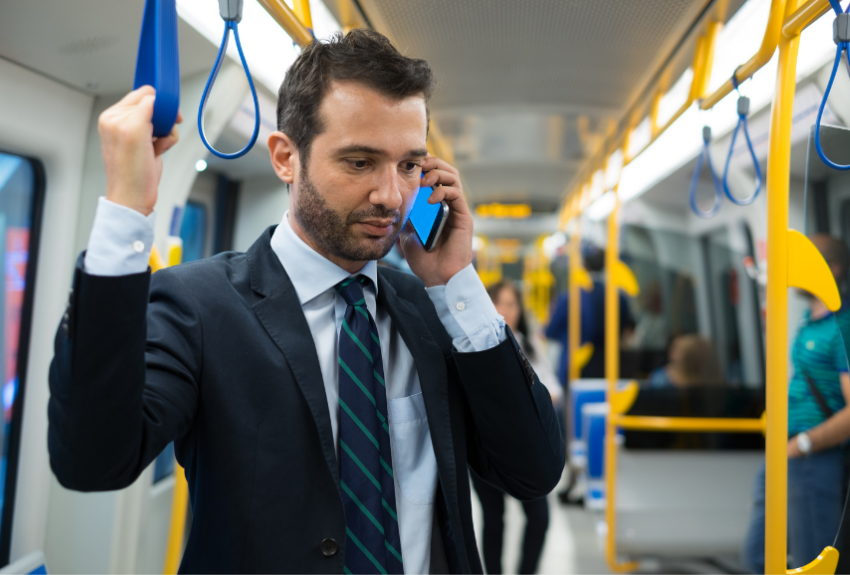 man-in-suit-on-train-talking-on-mobile-phone.png